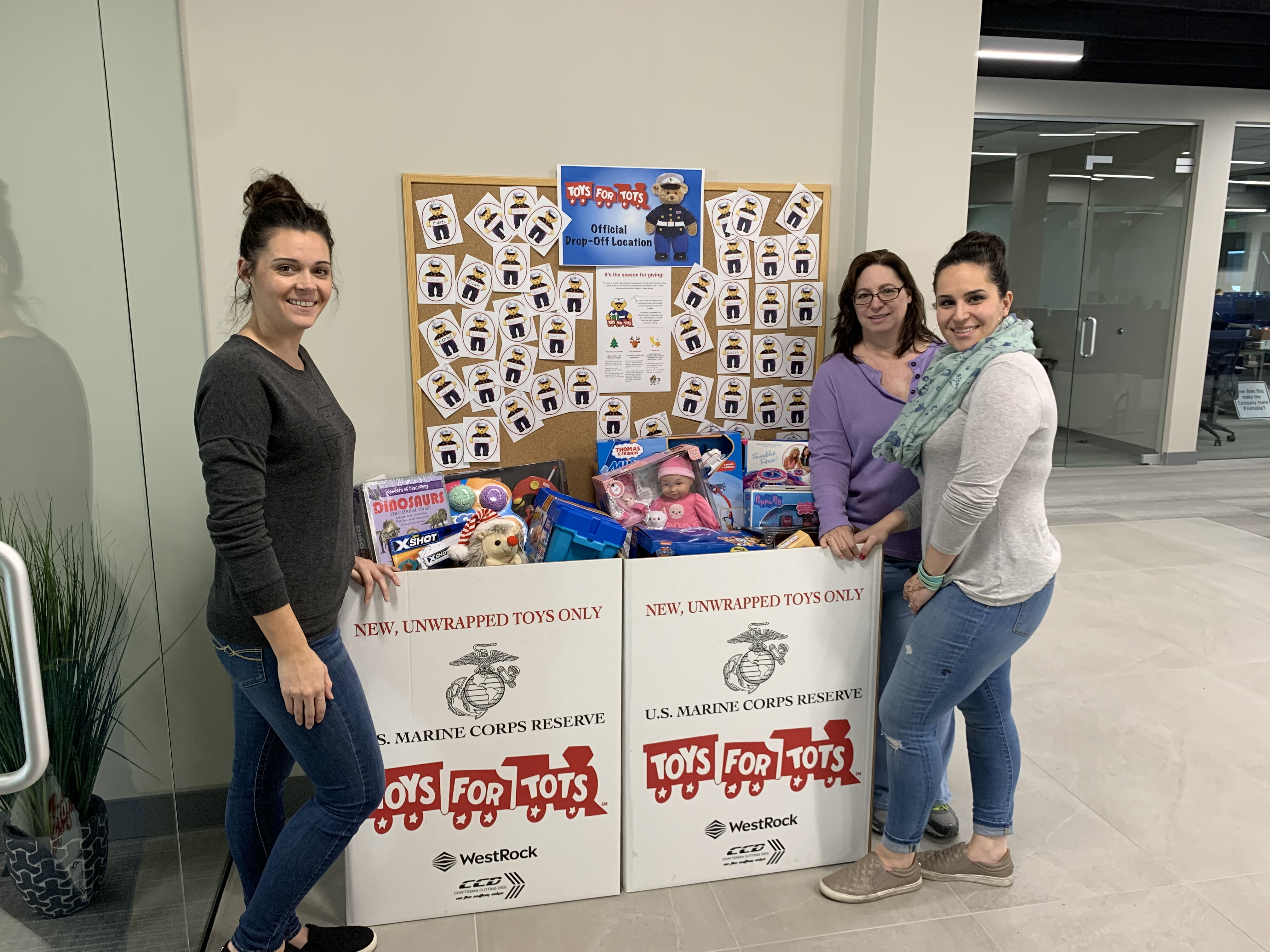 GlobalMed employees with the toys for tots boxes during the holidays